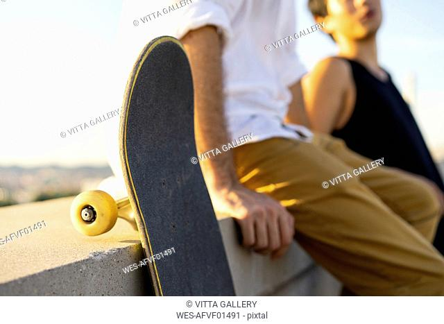 Close-up of two young men with skateboards sitting on a wall