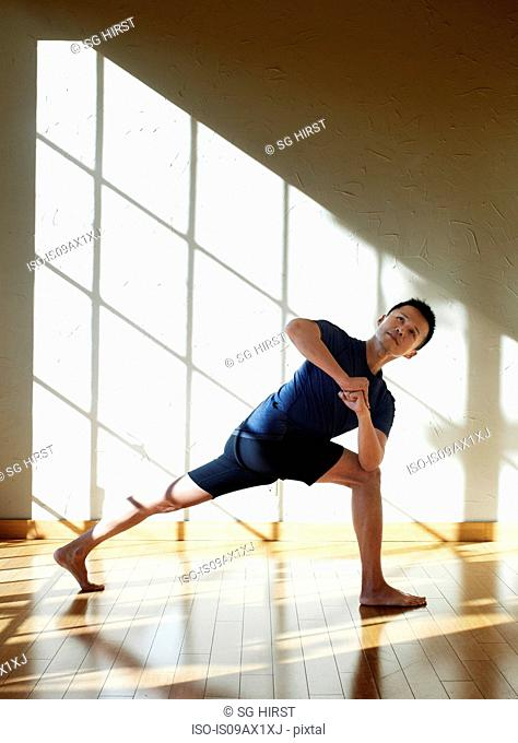 Man doing yoga in studio, in twisted prayer position