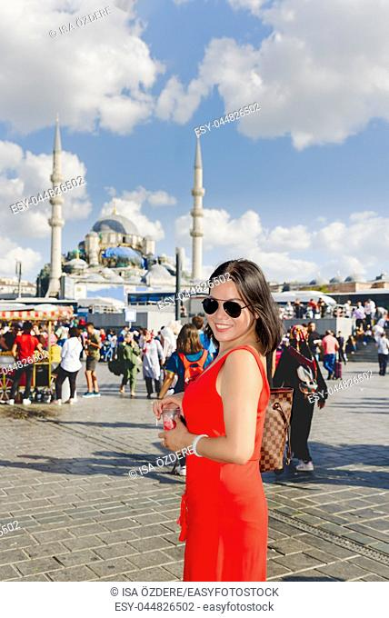 Beautiful Chinese woman poses at at Eminonu district with view of Suleymaniye mosque in Istanbul