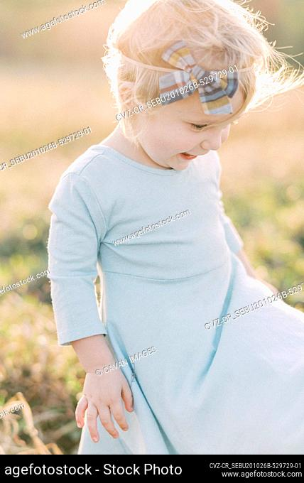 A toddler girl watching her dress fly in the wind