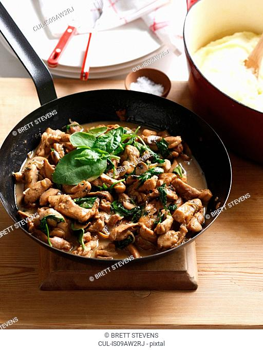 One pot chicken with spinach and mushrooms and a bowl of mashed potato