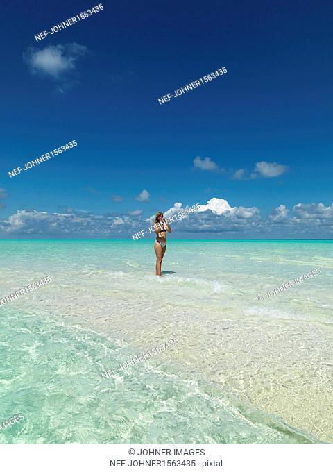 Woman taking photos on tropical beach