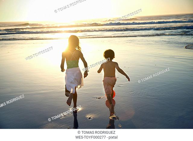 Boy and girl running on beach at sunset
