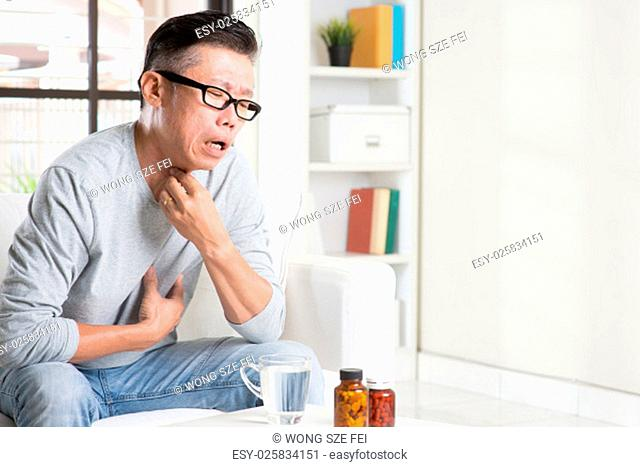 Casual 50s mature Asian man sore throat with painful face expression, hand on neck clearing throat, indoor home living lifestyle