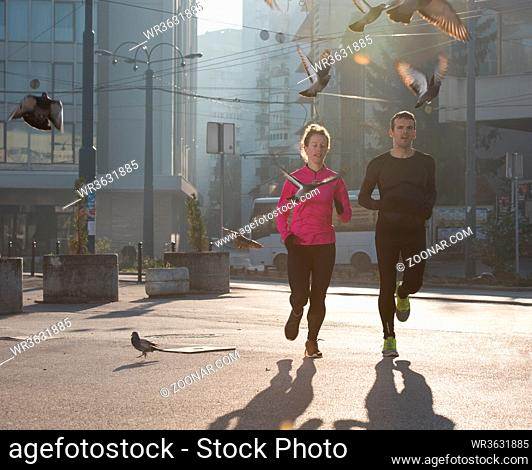 healthy young couple jogging in the city at early morning with sunrise in background