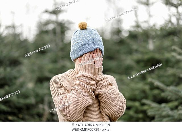 Boy wearing woolen hat covering his face