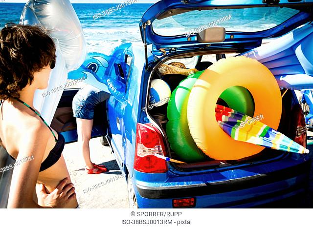 Woman unloading beach toys from car