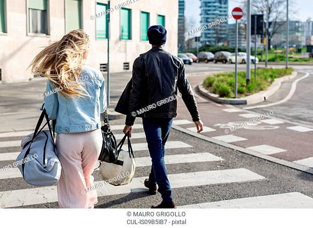 Young man and woman, crossing road carrying holdalls, rear view