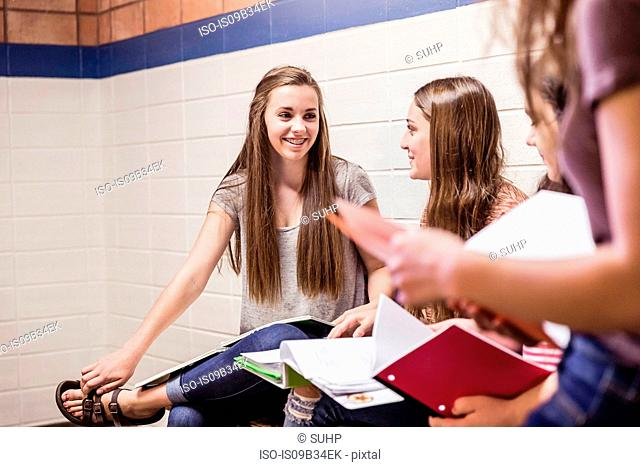Teenage high school girls in corridor talking and reading notes