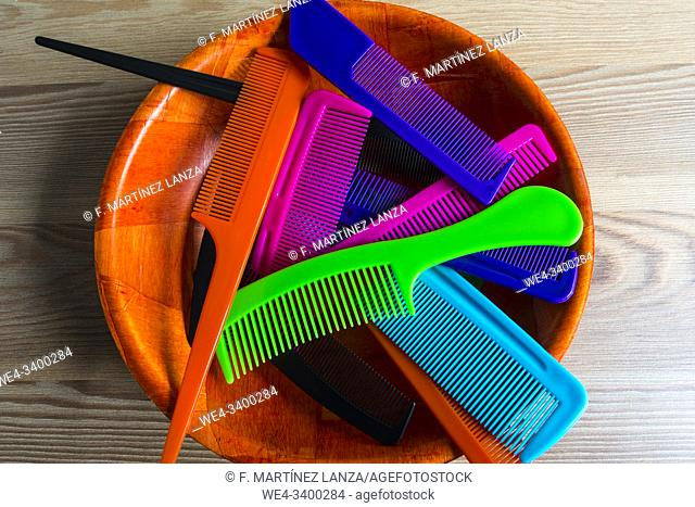 Colorful combs in wooden bowl