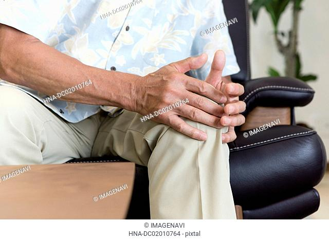 A senior man covering his hand on his genicula