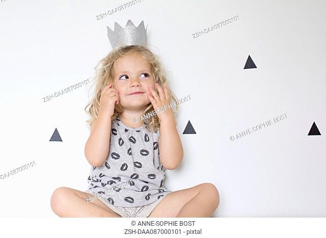 Little girl wearing a paper crown