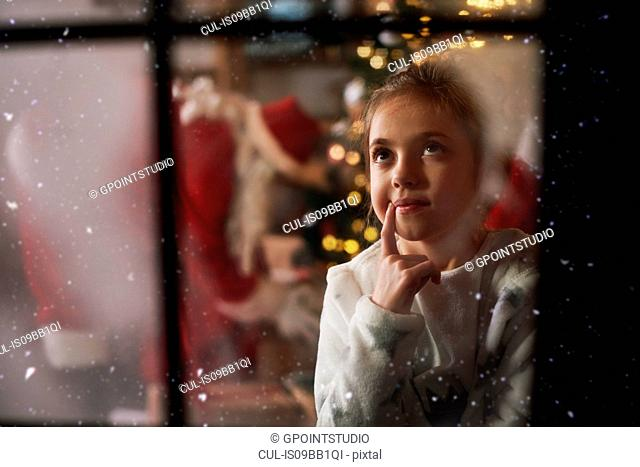 Young girl looking out of window on Christmas eve, Santa in background leaving gifts beside tree