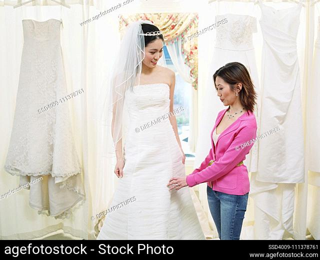 Young woman helping bride-to-be try on her gown