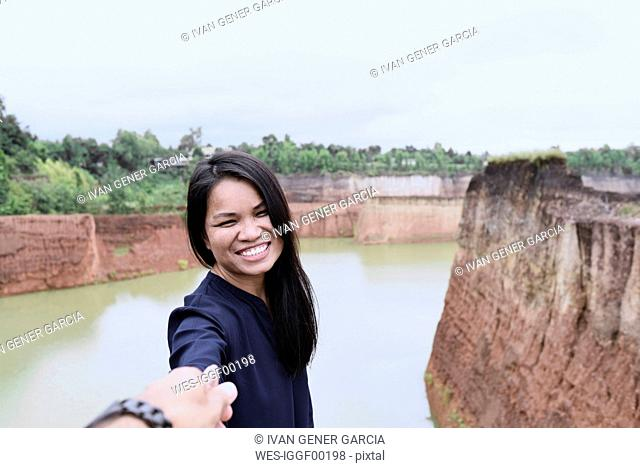 Thailand, Chiang Mai, happy young woman holding hand of her partner at grand canyon