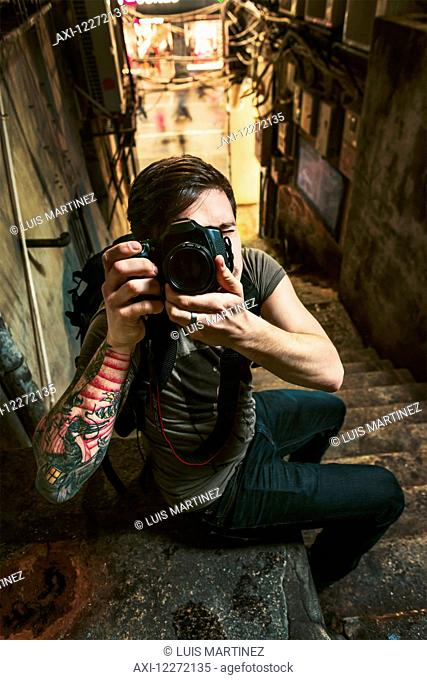 A male traveler taking a photograph with his camera in a narrow street; Xiamen, Fujian, China