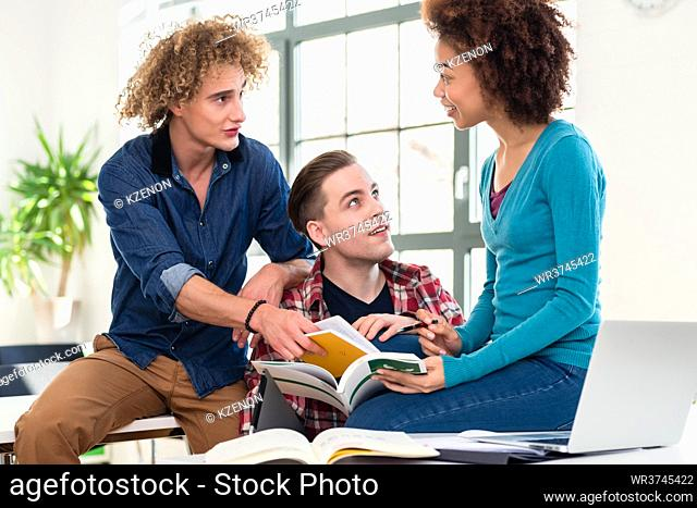 Three students sharing ideas and opinions while comparing information from two different textbooks during break at college