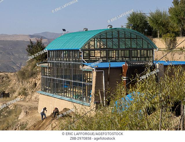 Traditonal tibetan wooden house covered with glass protection to keep the warmth in winter, Tongren County, Rebkong, China