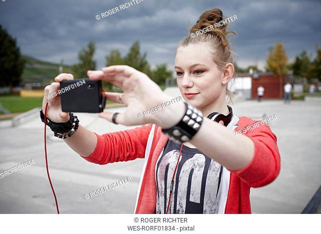 Teenage girl taking a selfie at a skatepark