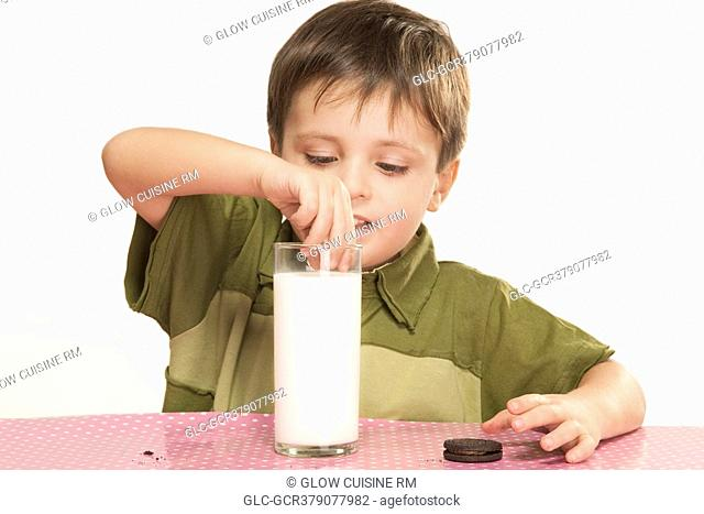 Close-up of a boy dunking cookies into milk