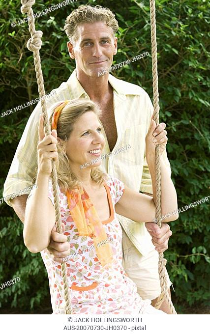 Mature man pushing a mature woman on a rope swing