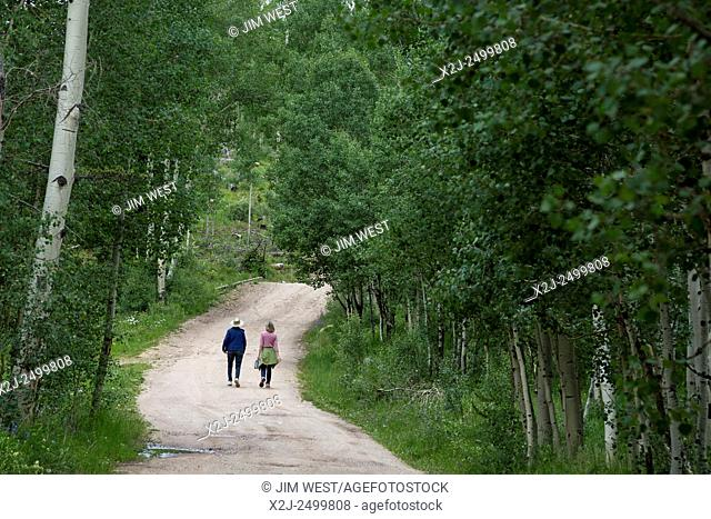 Silverthorne, Colorado - Two women hike along a road on the edge of the Eagles Nest Wilderness Area in White River National Forest