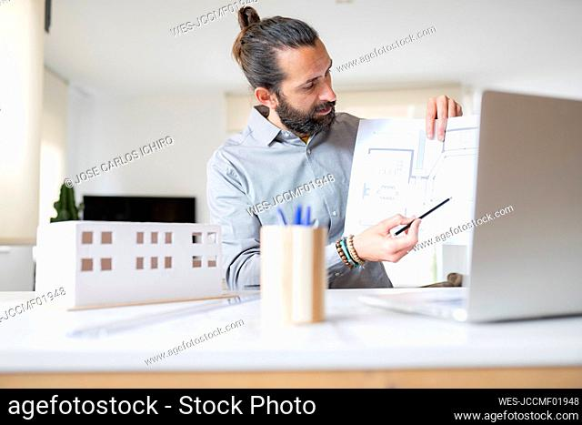 Male architect explaining construction plan over video call on laptop at home