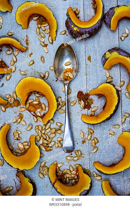 High angle close up of silver tablespoon and slices of pumpkin on blue background