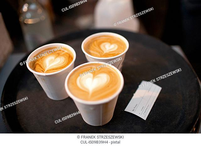 Three takeaway cups of coffee with heart shaped tops