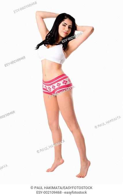 Beautiful in shape healthy happy young woman standing tiptoe stretching wearing white underwear shirt and pink hotpants, isolated