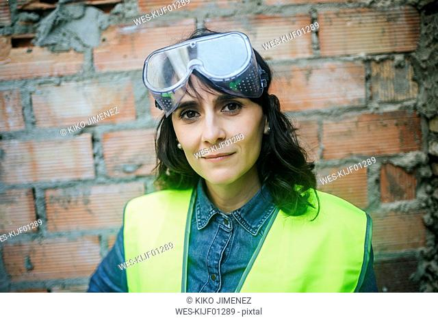 Portrait of confident woman wearing safety glasses on construction site