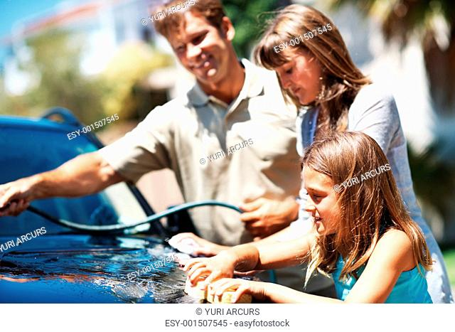 Young girl washing car with her father and sister