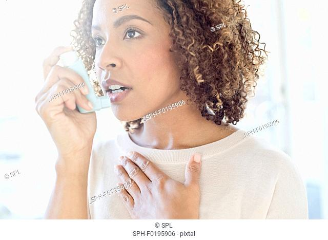 Mid adult woman using inhaler