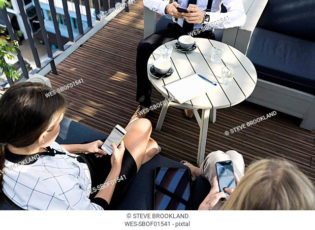 Three business colleagues having a coffee break on city terrace checking smartphones