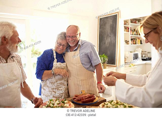 Affectionate senior couple enjoying pizza cooking class