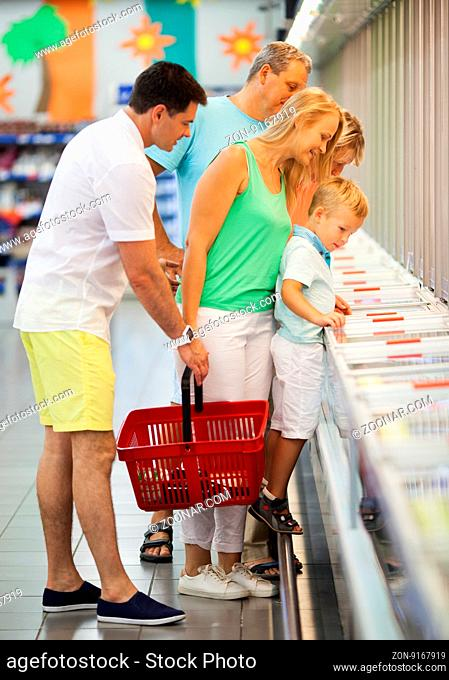 Family of three generations shopping together in a supermarket checking a a food display with the small boy standing up on the railing for a better view