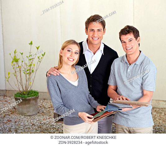 Glückliches Paar beim Teppichleger sucht einen Teppich aus verschiedenen Mustern aus