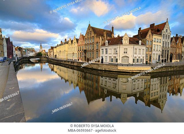 Pink clouds at dawn on the Belfry and historic buildings reflected in the typical canal Bruges West Flanders Belgium Europe