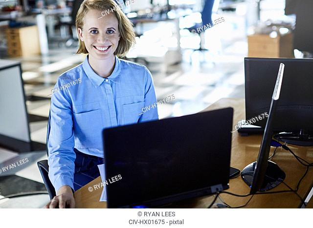 Portrait smiling businesswoman working at laptop in office