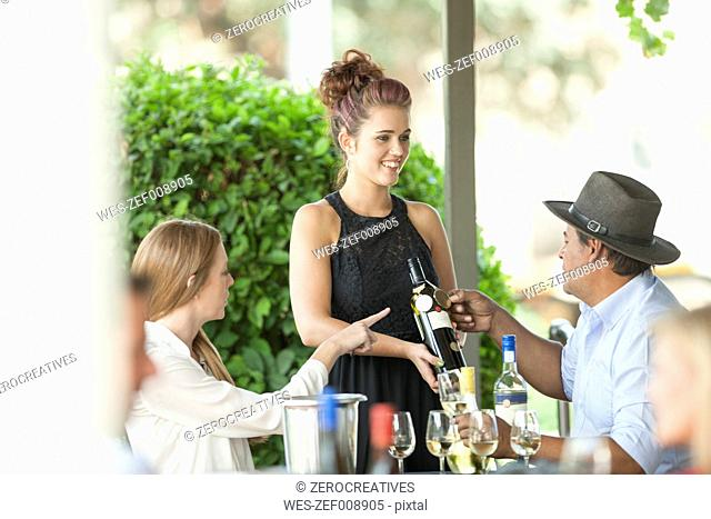 Waitress in restaurant showing wine bottle to man