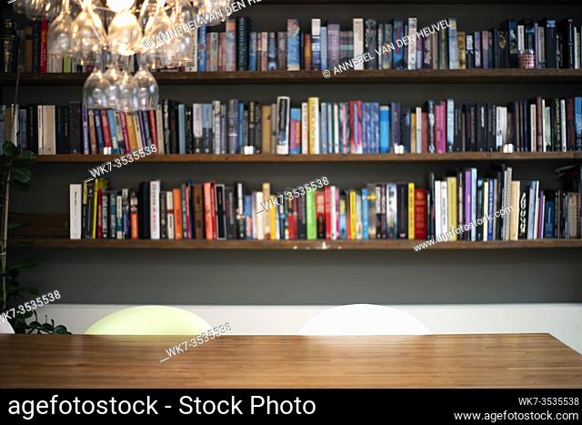 Coloful wall with many books on book shelves in a modern living room blurred, retro interior beauty