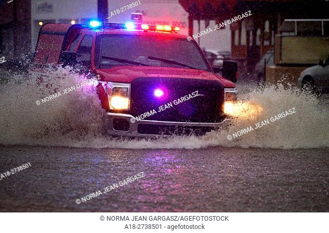 An emergency services vehicle drives through flooded streets during a monsoon storm, Sonoran Desert, Tucson, Arizona, USA