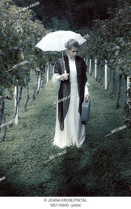 a woman in a white edwardian dress is walking with an umbrella and a suitcase in a vineyard
