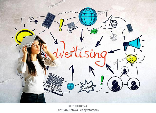 Worried young woman covering head with laptop on concrete background with colorful sketch. Advertising concept