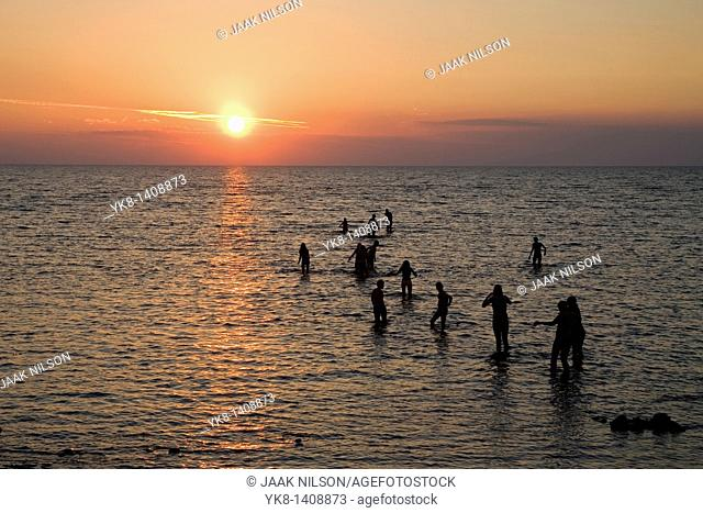 People Silhouettes in Water Against Sun