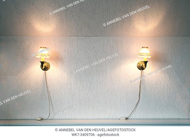 Two vintage lamps on the wallpaper . Wall light of gilded metal with two electric candles retro