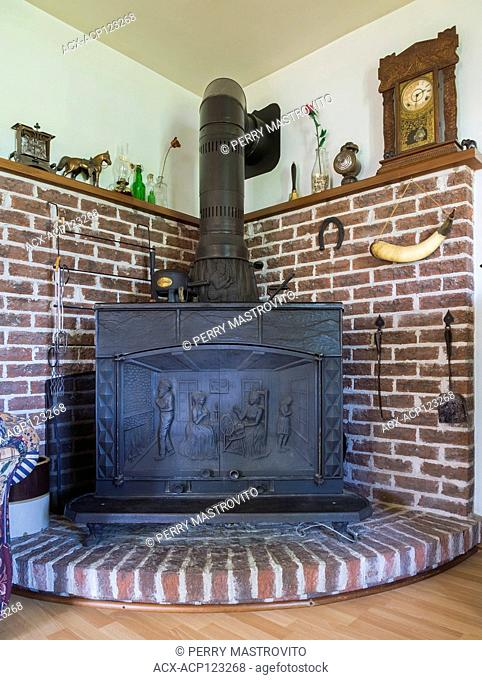 1977 Franklin reproduction wood stove mounted on elevated brick platform in living room inside an old 1927 Canadiana cottage style home, Quebec, Canada