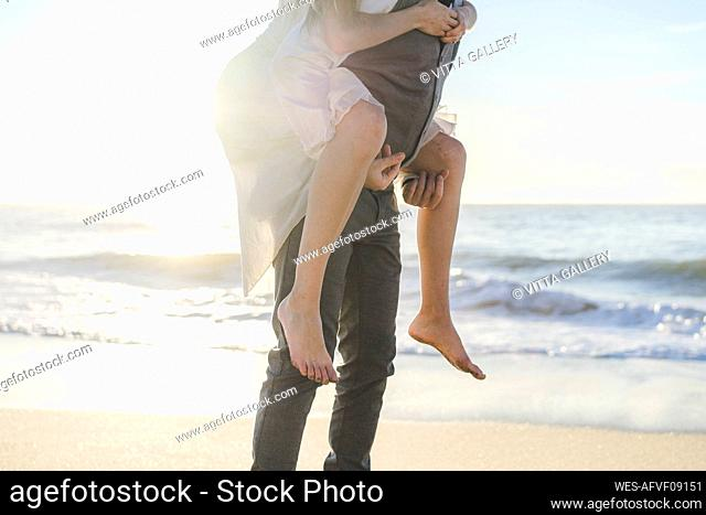 Young groom giving piggyback ride to bride at beach
