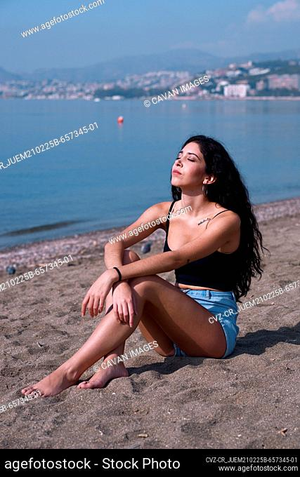 Attractive arabic woman in shorts sitting on the sand in the sun