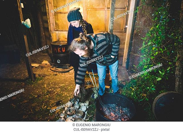 Couple using tongs to remove clay pots from fire, smiling